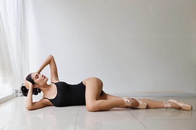 Mooie balletdanser, aziatisch model dat op witte muurstudio danst