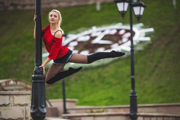 Mooie balletdanseres of acrobatische dans buiten in de straat