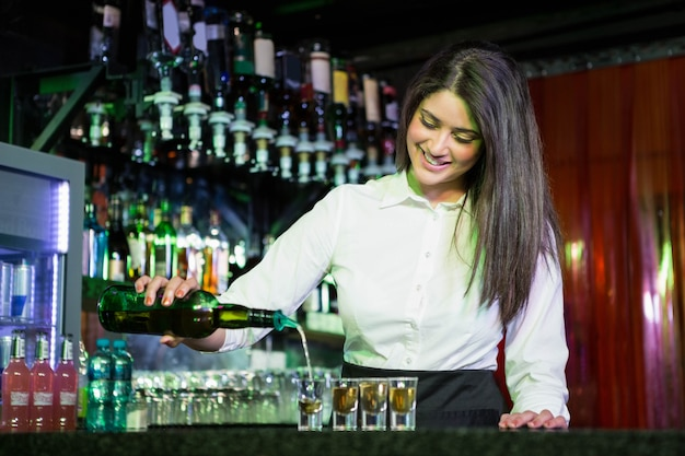 Mooie barman die tequila gieten in glazen bij barteller