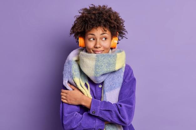 Mooie bedachtzame afro-amerikaanse vrouw omhelst zichzelf warm draagt een sjaal om de nek aangenaam geconcentreerd opzij terwijl ze muziek luistert via een draadloze koptelefoon.