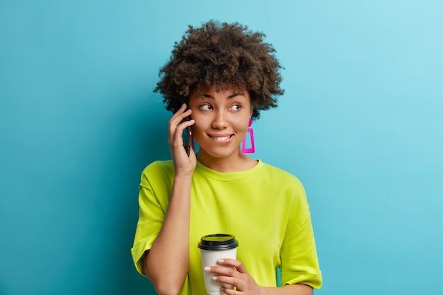 Mooie bedachtzame vrouw met donkere huid heeft telefoongesprek geconcentreerd opzij bijt nadenkend bijt lippen drinkt afhaalkoffie