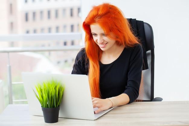 Mooie bedrijfsdame die met laptop in bureau werkt.
