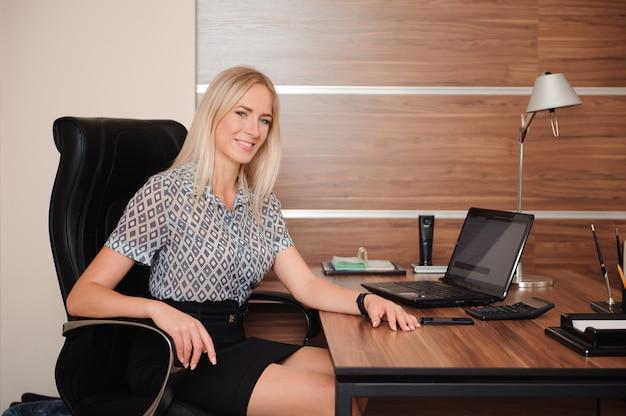 Mooie bedrijfsvrouw die met verkoop in haar bureau werkt