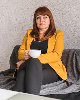 Mooie bedrijfsvrouw die van koffie geniet