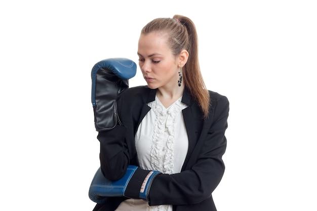 Mooie bedrijfsvrouw die zich in bokshandschoenen bevindt die zijn hoofd hangen dat op witte muur wordt geïsoleerd