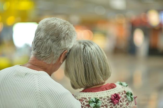 Mooie bejaarde echtpaar achterkant in winkelcentrum