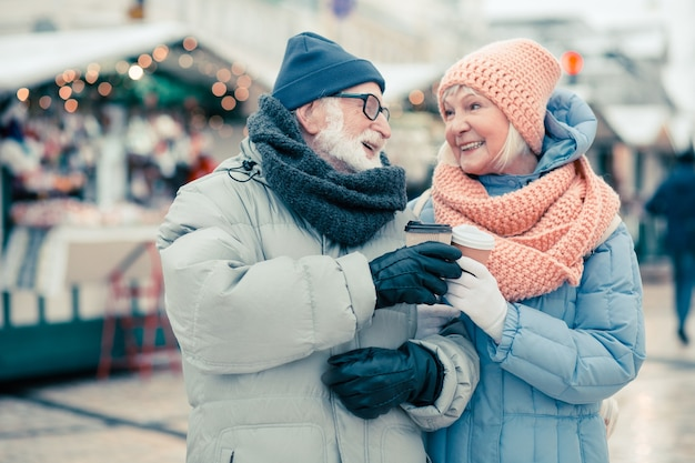 Mooie bejaarde echtpaar in winterkleren die tijd buitenshuis doorbrengen en naar elkaar glimlachen terwijl ze hun kartonnen kopjes koffie kletteren