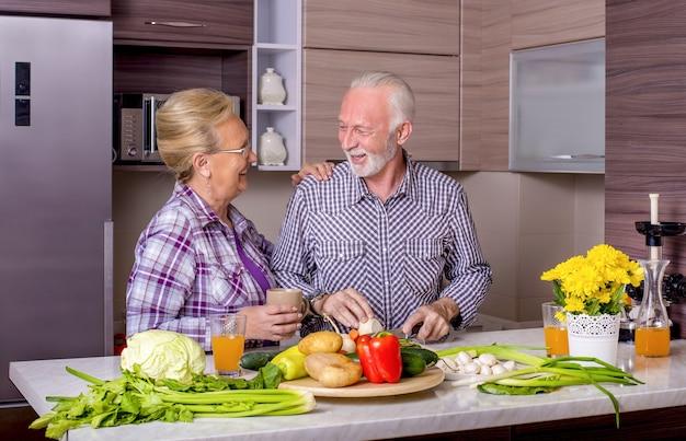 Mooie bejaarde echtpaar koken in de keuken met elkaar