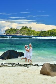 Mooie bejaarde echtpaar staande op het strand omarmen
