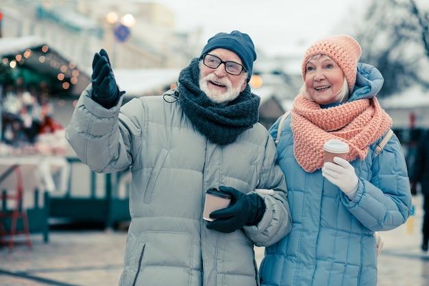 Mooie bejaarde echtpaar wandelen in de winterdag en genieten van koffie. man gebaren met zijn rechterhand en wijzend naar de verte