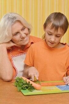 Mooie bejaarde vrouw en een jongen in de sinaasappel in de keuken
