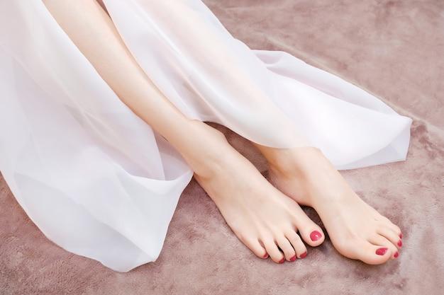 Mooie benen van een jonge vrouw onder een luchtige zijden stof. voet huidverzorging