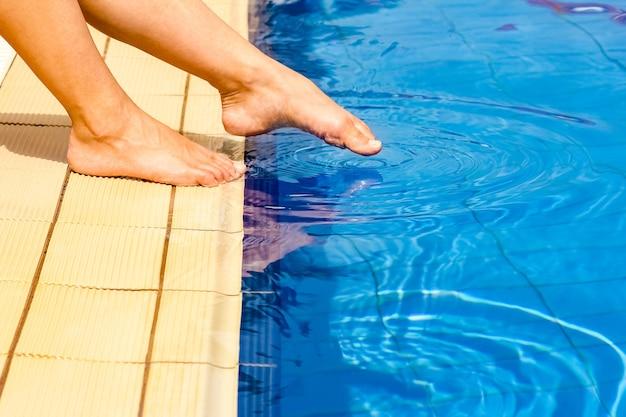 Mooie benen van een meisje in de buurt van een zwembad op het zeeoppervlak
