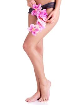 Mooie benen van vrouw na kuuroordsalon met bloem - die op witte achtergrond wordt geïsoleerd