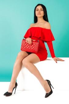 Mooie benen vrouw, gekleed in rode jurk met tas handtas met hoge hakken schoenen zittend op de witte bank