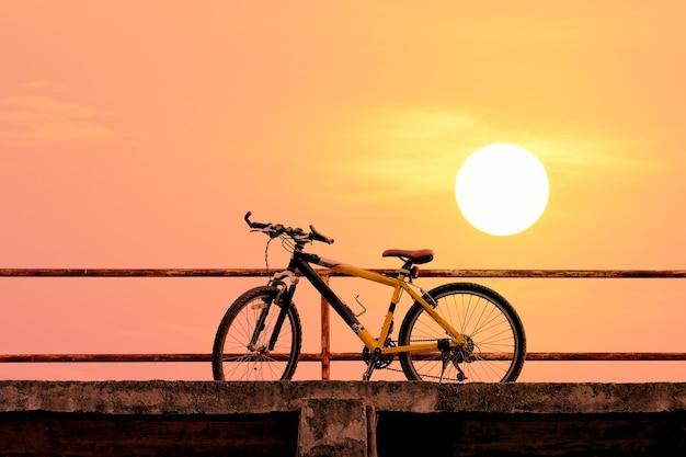 Mooie bergfiets op betonnen brug met kleurrijk zonlicht; vintage filterstijl voor wenskaart en postkaart.