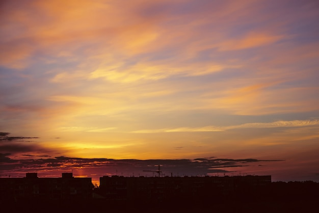 Mooie bewolkte dramatische ochtendhemel boven silhouet van stadsgebouwen. pittoreske dageraad in de stad. achtergrond van varicolored wolken.