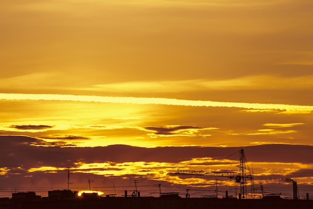 Mooie bewolkte dramatische ochtendhemel boven silhouet van stadsgebouwen. pittoreske dageraad in de stad