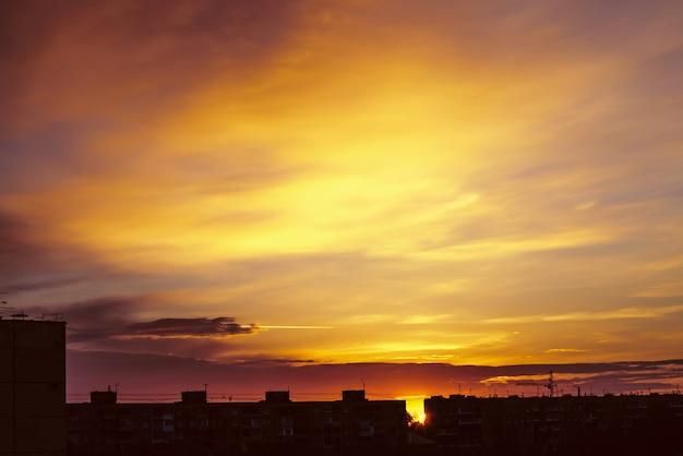 Mooie bewolkte dramatische ochtendhemel boven silhouet van stadsgebouwen