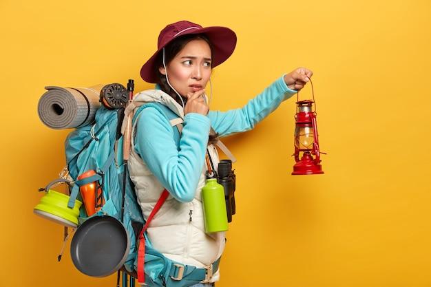 Mooie bezorgde vrouwelijke toerist draagt een zware rugzak, houdt rode lantaarn vast voor blikseminslag in de duisternis