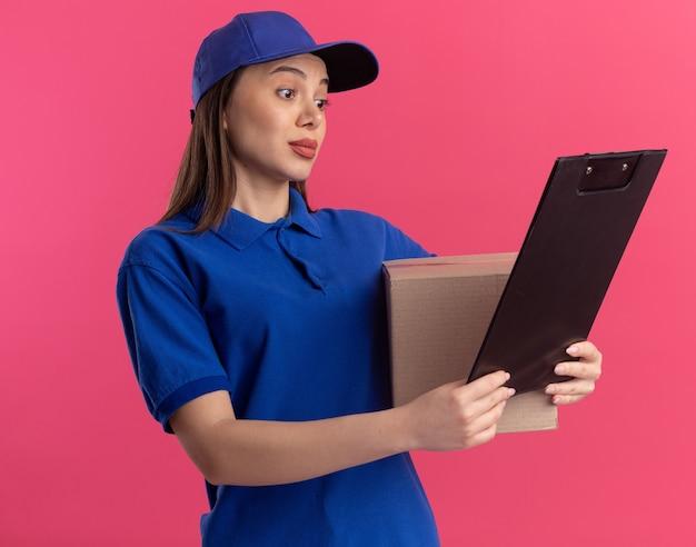 Mooie bezorger onder de indruk in uniform houdt kartonnen doos en kijkt naar klembord op roze