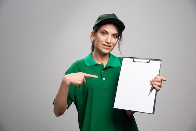 Mooie bezorgvrouw in groen uniform wijzend op klembord.