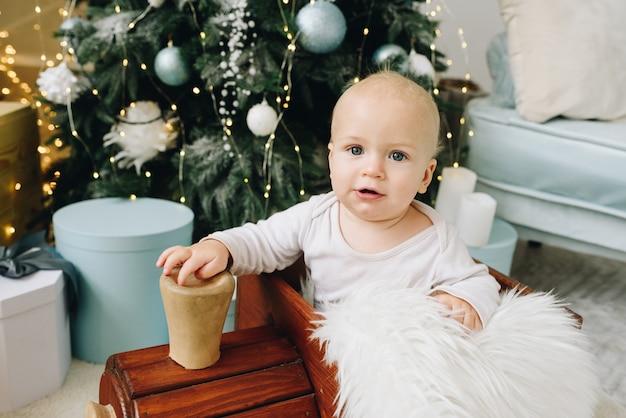 Mooie blanke baby zittend in een houten speelgoed trein in de buurt van versierde kerstboom