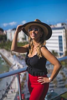 Mooie blanke blanke vrouw staat gelukkig op het balkon met uitzicht op zee