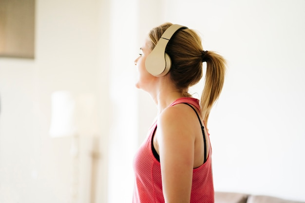 Mooie blanke blonde vrouw oefeningen op een loopband in haar woonkamer