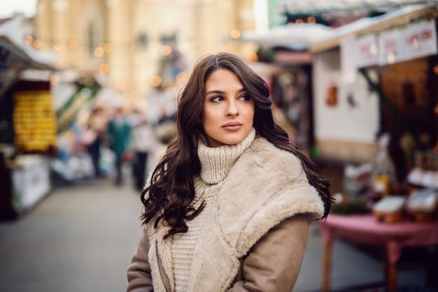 Mooie blanke brunette in jas staande op straat en wegkijken.