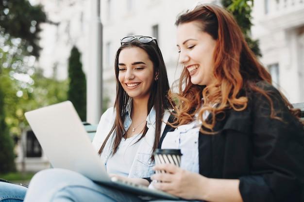 Mooie blanke brunette met lang haar lachend terwijl ze naar de laptop van haar vriendinnen kijkt, die ook zittend op een bankje tegen een luxe gebouw lachend is.