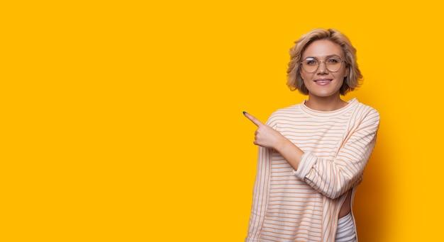 Mooie blanke dame met blond haar die een bril draagt, wijst naar rechts terwijl ze poseren op een gele, lege, uit elkaar geplaatste achtergrond