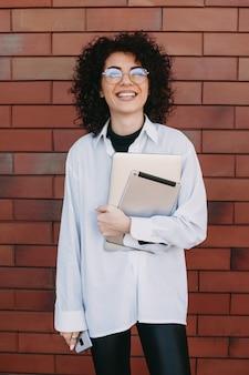 Mooie blanke dame met krullend haar en moderne gadgets is poseren op een stenen muur terwijl glimlachen