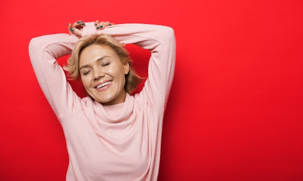 Mooie blanke dame poseren met handen omhoog op een rode muur met vrije ruimte
