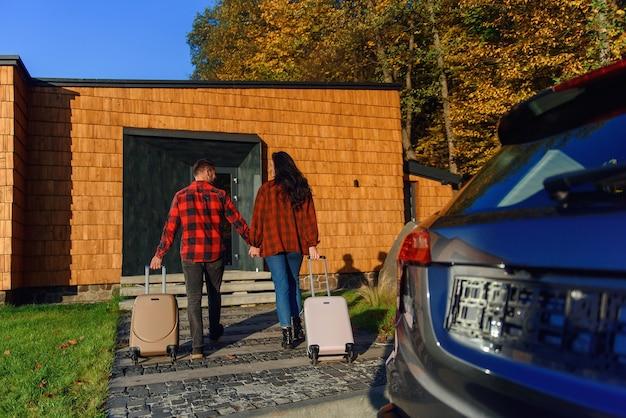 Mooie blanke familie die naar een nieuw huis verhuist, gaat met koffers naar een nieuw huis.