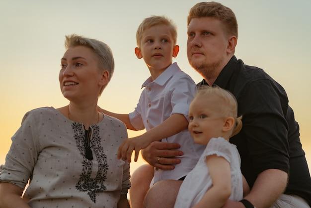 Mooie blanke familie met moeder die een kind verwacht, geniet van zonsondergang op het strand