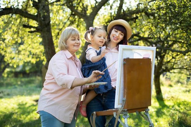 Mooie blanke familie van drie generaties, grootmoeder, moeder en klein schattig kindmeisje, buiten in het lentepark in de zomer en een foto schilderend op houten ezel.