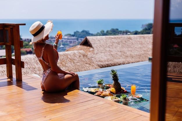 Mooie blanke gelooide vrouw in bikini en strooien hoed met drijvend ontbijt in geweldige luxe villa in bali-stijl op zonnige dag bij zwembad, tropische achtergrond.