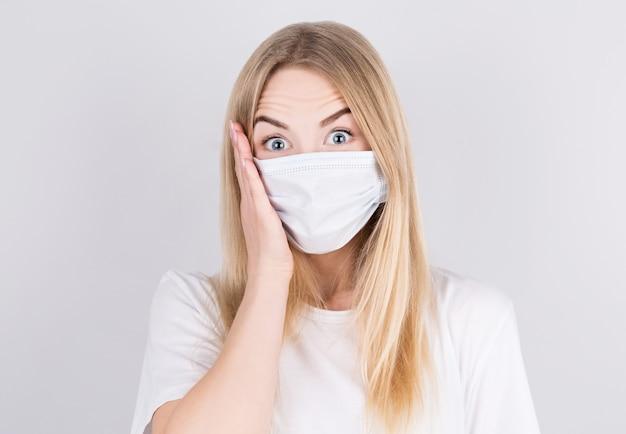 Mooie blanke jonge vrouw in wit t-shirt met wegwerp gezichtsmasker verrast