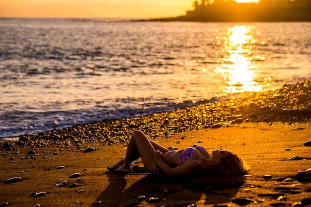 Mooie blanke jonge vrouw neemt de zon en ontspant zich op het strand tijdens de zonsondergang aan het einde van een dag vakantie. oceaan natuur buitenactiviteit voor schattige dame die geniet van de levensstijl in de buurt van de oceaan