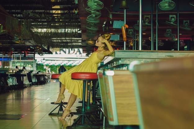 Mooie blanke jonge vrouw poseren in een gele zomerjurk, zonnebril en kinderachtig broodje kapsel aan de gesloten bar in pattaya.