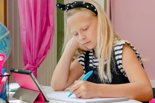 Mooie blanke linkshandige schoolmeisje verveeld tijdens haar huiswerk. onderwijs concept.