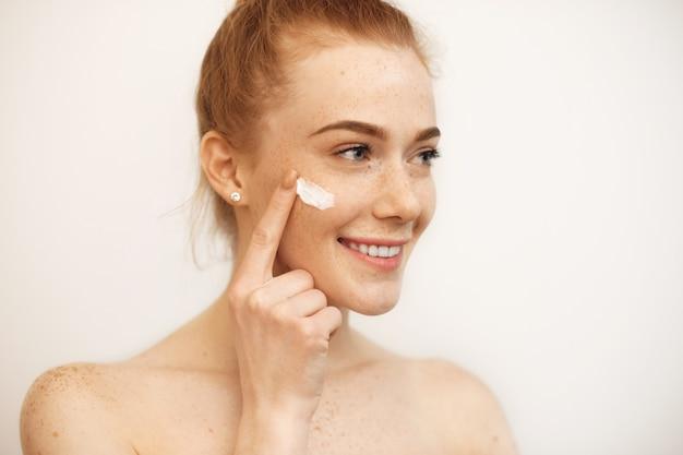Mooie blanke meisje met rood haar en sproeten lacht tijdens het gebruik van een crème op haar gezicht