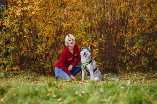 Mooie blanke meisje speelt met husky hond in herfst bos of park