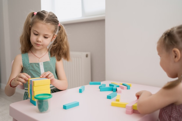 Mooie blanke meisjes spelen met houten veelkleurige blokken