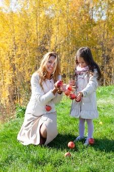 Mooie blanke moeder, dochtertje spelen met rijpe rode appels op achtergrond van groen gras van gouden bomen van herfst bos. concept familieweekend buitenshuis, mensen, weer, levensstijl
