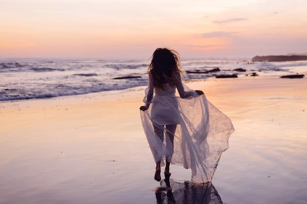 Mooie blanke vrouw alleen in witte jurk bij paarse zonsondergang door oceaan
