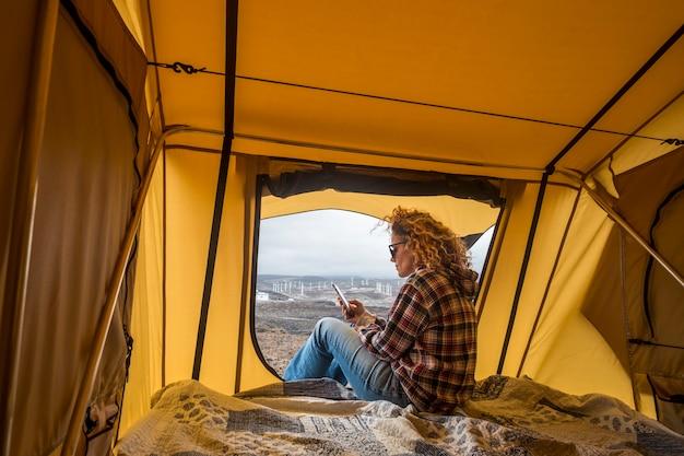 Mooie blanke vrouw controleert de smartphone op internetcontacten en werkt terwijl ze buiten een tent gaat zitten met uitzicht op de oceaan