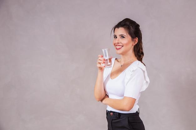Mooie blanke vrouw die een glas water drinkt.