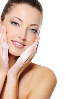 Mooie blanke vrouw die haar gezicht van de schoonheidsgezondheid met schuim op haar handen wast